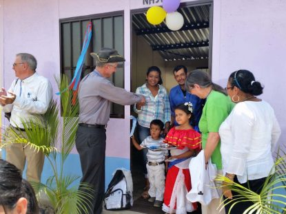 Father Paul Kennedy applauds after Deacon Peter cuts the ribbon on a new home in Jicaro, Nicaragua.