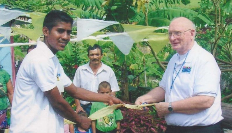 Msgr. Francis Schmidt (right) and a resident of a village in Nicaragua cut the ribbon on the latest project of Father chuck's Challenge to provide homes for needy families.