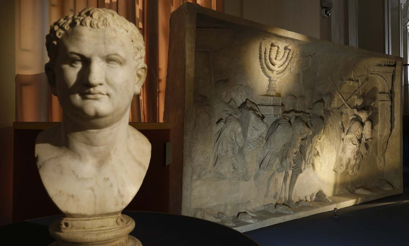 A bust of Roman Emperor Titus is pictured next to a replica of the 1st-century Arch of Titus, showing Roman soldiers carrying the menorah, in a exhibition at the Vatican May 15. The replica of the Arch of Titus is the central motif in a two-part exhibition on the menorah at the Vatican and at the Jewish Museum in Rome. (CNS photo/Paul Haring)