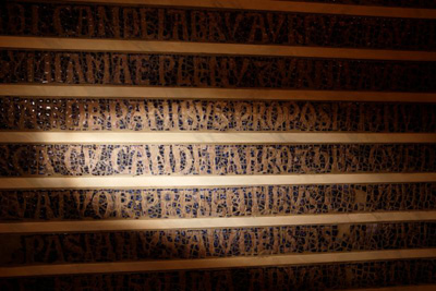 """The Latin word, """"candelabro,"""" believed to refer to the menorah taken by the Romans from Jerusalem in the 1st century, is seen on a 37-line mosaic inscription from the 13th century at the Jewish Museum in Rome May 15. The inscription describes treasures supposedly buried under the Basilica of St. John Lateran in Rome. The inscription is part of a two-part exhibition on the menorah at the Vatican and at the Jewish Museum. (CNS photo/Paul Haring)"""