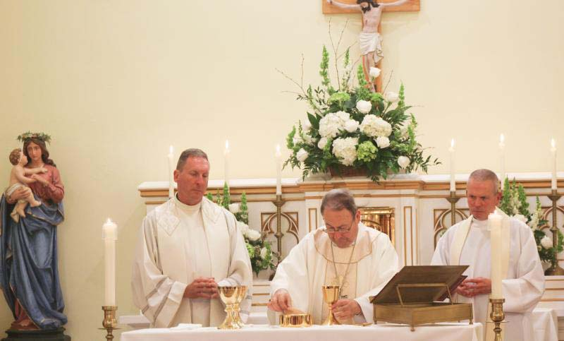 Bishop Robert E. Guglielmone of Charleston, S.C., center, concelebrates a 100th anniversary Mass at St. Francis of Assisi Mission in Walhalla, S.C., with Fathers Gregory West and William Hearne. (CNS photo/Christina Lee Knauss, The Catholic Miscellany)
