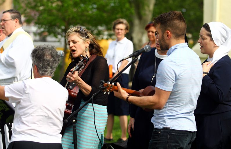 Musicians lead a hymn of praise during Mass on a windy Saturday afternoon in the park.