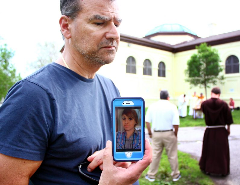 Joseph Giandonato shows a picuture of his daughter Alissa, who he lost to addiction. He offered prayers for her for during Mass in McPherson Square Park.