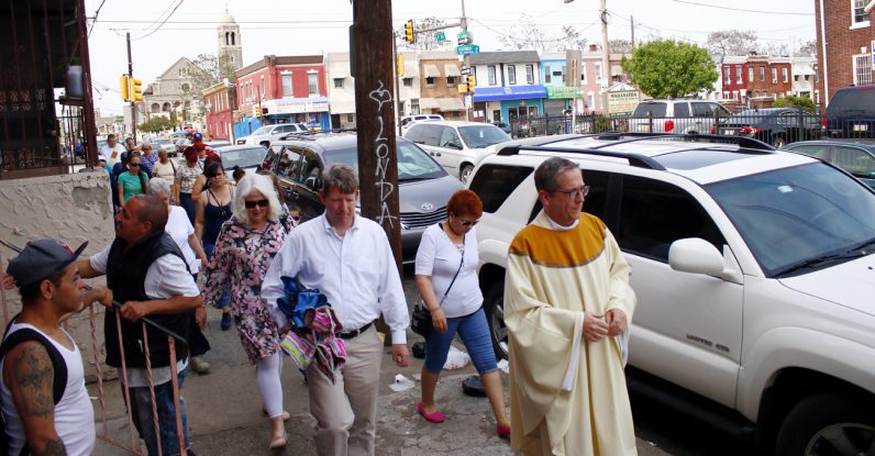 Father Liam Murphy walks with people of the community to McPherson Square Park from Mother of Mercy House, seen in the background. Behind it far in the background sits the looming Ascension of Our Lord Church, which as been closed and vacant for five years.