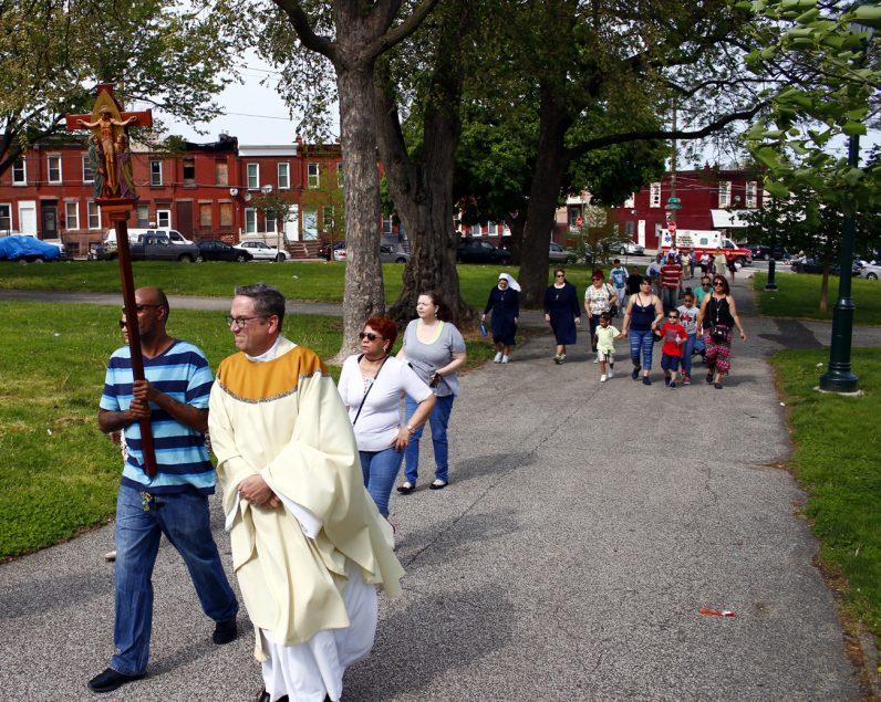 Victor Colon and Father Liam Murphy lead the procession through McPherson Square Park for Mass.