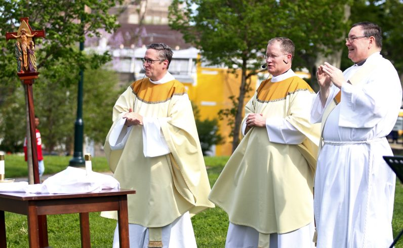 Fathers Liam Murphy and Father Joseph Devlin celebrate Mass in McPherson Square Park as Deacon Steve Guckin assists.