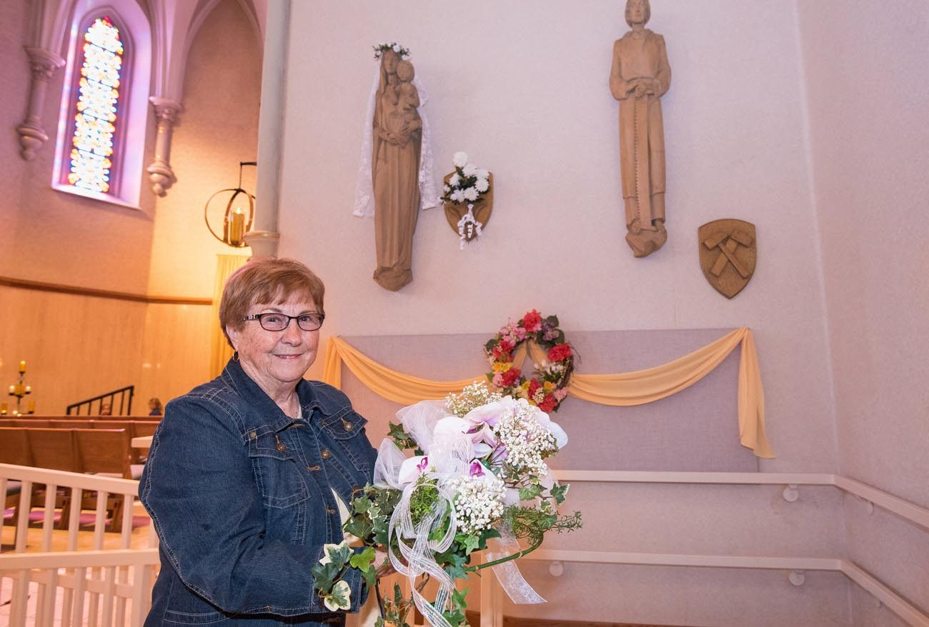 Karen Mulry holds a purple orchid corsage, similar to one placed on the statue of Mary, seen in the background May 4, at St. John Nepomucene Church in Little Chute, Wis. An anonymous request to place flowers on the statue for Mother's Day has been sent to Reynebeau Floral in Little Chute for 70 years. (CNS photo/Sam Lucero, The Compass)