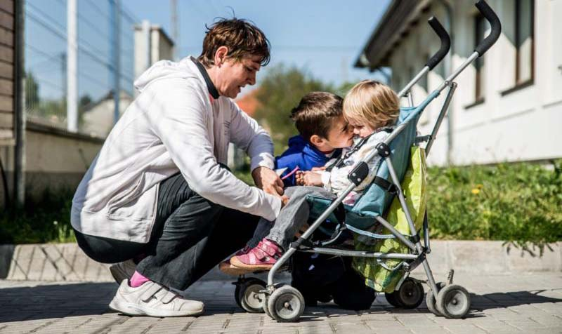 A mother gets her children ready for a walk in Erd, Hungary, April 30, 2016. Whether through birth or adoption, motherhood is a labor of love. (CNS photo/Zoltan Balogh, EPA)
