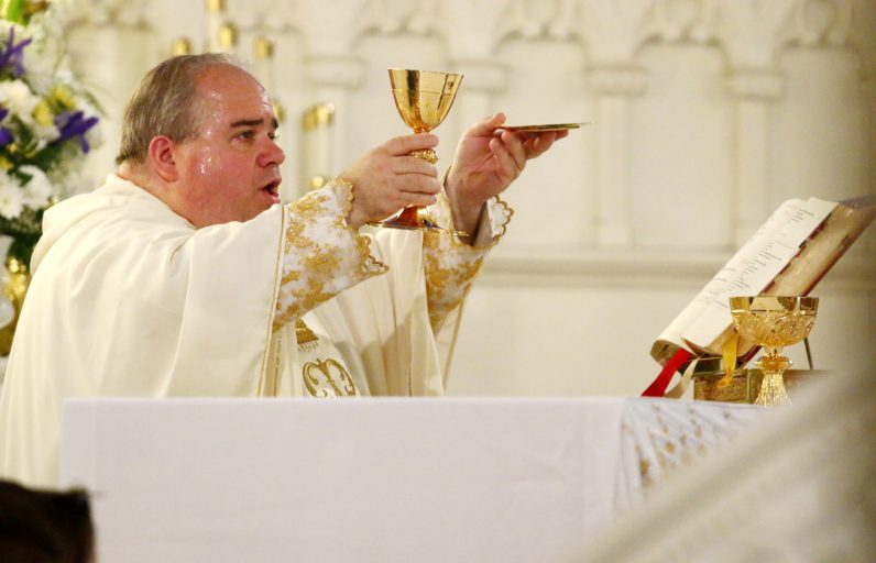 Father Michael Rock, O.deM., pastor of Our Lady of Lourdes Parish, celebrates Mass on April 30.