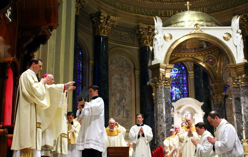 Archbishop Charles Chaput prays over the two men to be ordained priests during the ordination rite.
