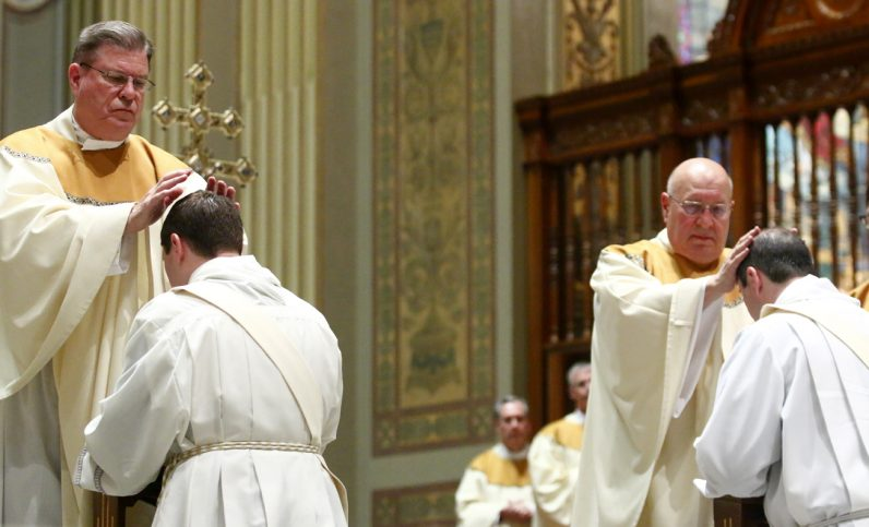 Msgr. John Conway, left, and Msgr. Charles Vance, pastors of the newly ordained priests, lay hands on them as part of the ordination ceremony.