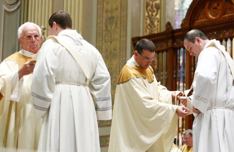 Msgr. Philip Ricci and Father Jeff Rott vest the newly ordained priests.