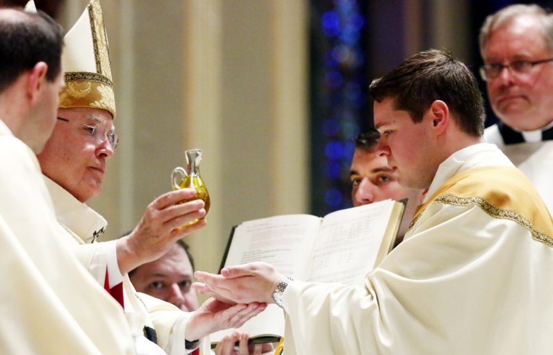 Archbishop Chaput pours the oil of sacred chrism into the hands of Father Matthew Brody.