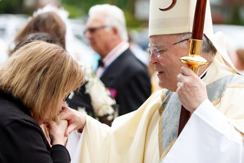A parishioner kisses the hand of Archbishop Charles Chaput following Mass at Our Lady of Fatima Church in Secane.