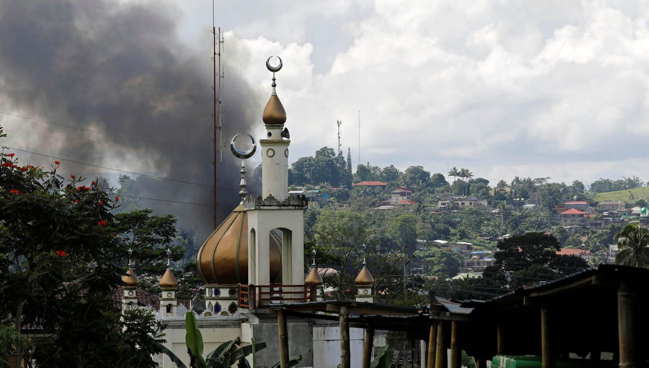 Smoke billows near a mosque in Marawi, Philippines, May 30. Catholic bishops in the southern Philippines supported the declaration of martial law in Mindanao following an attempt by a band of gunmen claiming to be Islamic militants to seize the city. (CNS photo/Erik De Castro, Reuters)