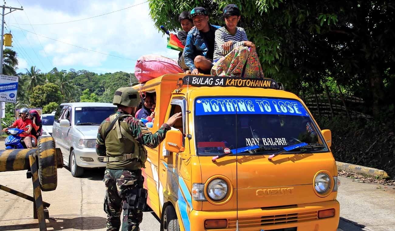 A Philippine government soldier inspects a vehicle May 24 at a checkpoint along a main highway in Lanao del Norte province. Residents started to evacuate the town of Marawi after President Rodrigo Duterte imposed martial law across the entire Muslim-majority region of Mindanao. (CNS photo/Romeo Ranoco, Reuters)