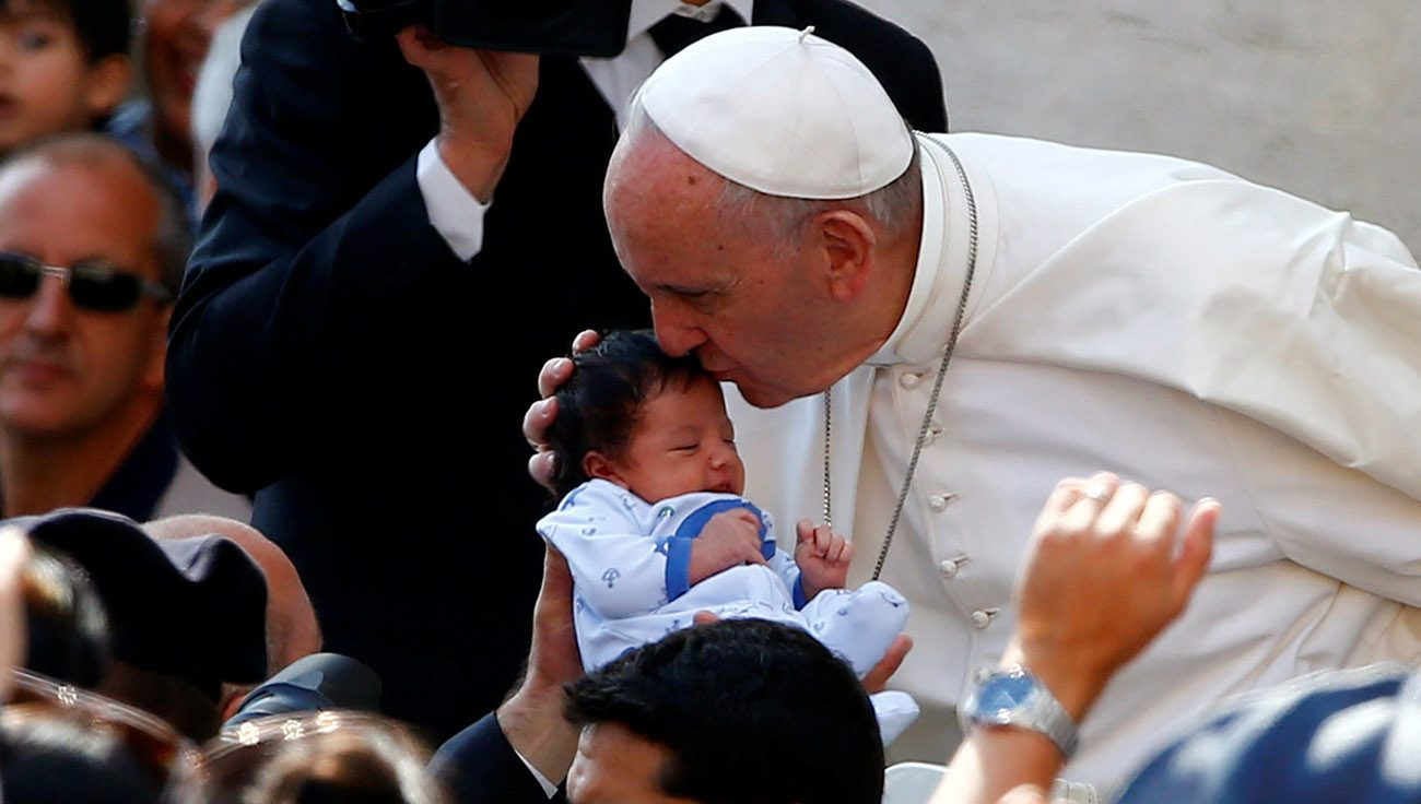 Pope Francis kisses a baby as he arrives to lead his general audience in St. Peter's Square May 10 at the Vatican. (CNS photo/Tony Gentile, Reuters)
