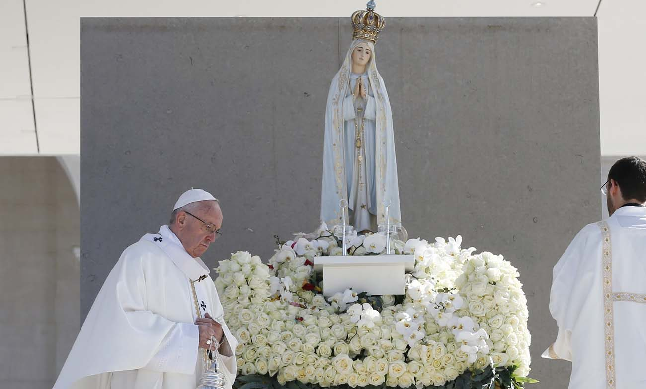 Pope Francis uses incense as he venerates a statue of Our Lady of Fatima during the canonization Mass of Sts. Francisco and Jacinta Marto, two of the three Fatima seers, at the Shrine of Our Lady of Fatima in Portugal, May 13. The Mass marked the 100th anniversary of the Fatima Marian apparitions, which began on May 13, 1917. (CNS photo/Paul Haring)