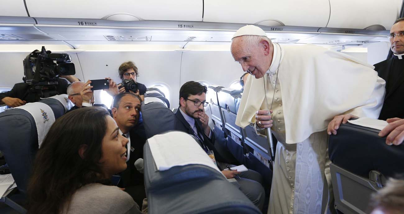 Pope Francis listens to a question from Joana Haderer of LUSA as he speaks with journalists aboard his flight from Portugal to Rome May 13. The pope made a two-day visit to Fatima to commemorate the 100th anniversary of the Marian apparitions and to canonize Sts. Francisco and Jacinta Marto, two of the young seers. (CNS photo/Paul Haring)