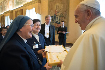 Pope Francis accepts a gift as he greets participants in the general chapter of the Sister Disciples of the Divine Master during an audience at the Vatican May 22. (CNS photo/L'Osservatore Romano)
