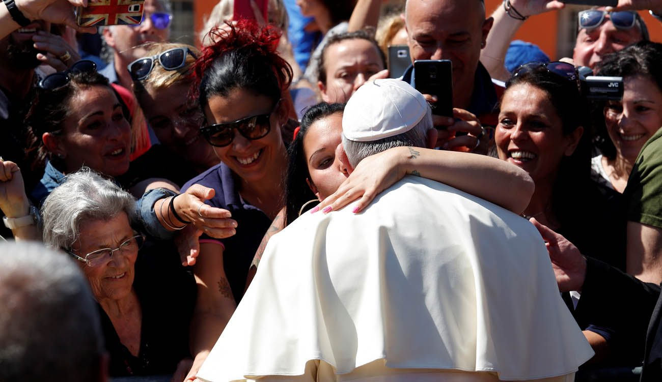 A woman kisses Pope Francis as he arrives for a visit at the parish of San Pier Damiani May 21 at Casal Bernocchi on the outskirts of Rome. (CNS/Remo Casilli, Reuters)