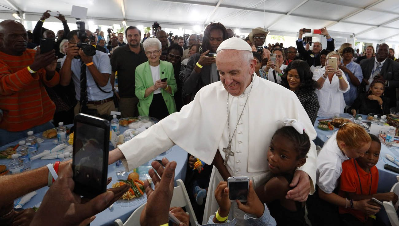 A girl hugs Pope Francis as he visits with people at St. Maria's Meals Program of Catholic Charities in Washington in this Sept. 24, 2015, file photo. (CNS photo/Paul Haring)