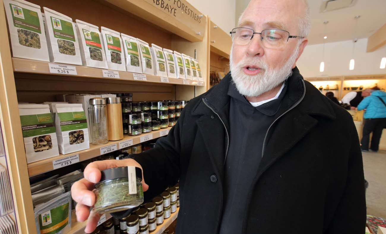 Abbot Andre Barbeau of Val Notre-Dame Cistercian abbey in Saint-Jean-de-Matha, Quebec, holds a jar of larch needles, used in salads and soups produced at the abbey and sold in its gift shop. (CNS photo/Philippe Vaillancourt, Presence)