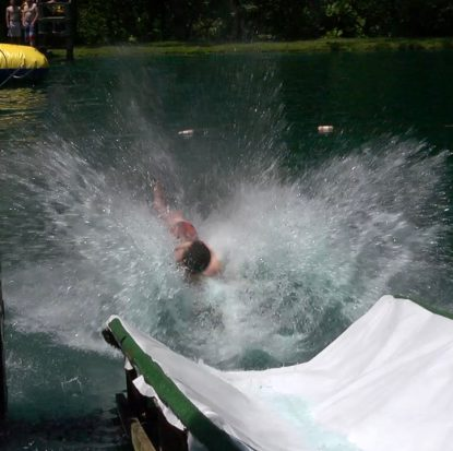 A boy takes a splash off a water slide at the Quo Vadis retreat.