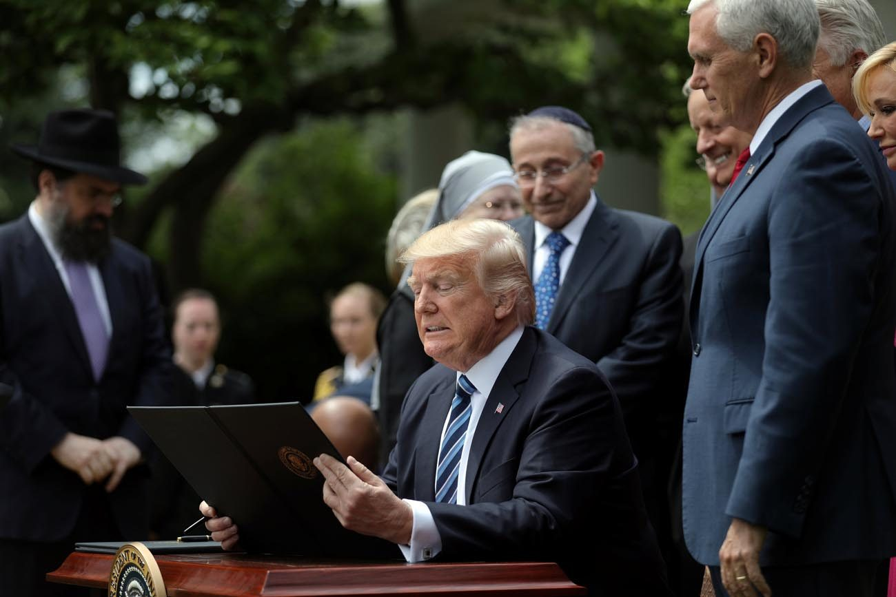 President Donald Trump prepares to sign his Executive Order on Promoting Free Speech and Religious Liberty during the National Day of Prayer event at the White House in Washington May 4. (CNS photo/Carlos Barria, Reuters)