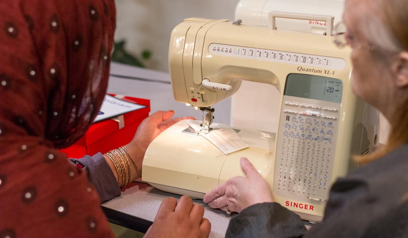 A volunteer works with a refugee from Afghanistan to help her learn how to use a sewing machine during an April 27 training session at a Catholic Charities program in Fredericksburg, Va. (CNS photo/Ashleigh Buyers, Catholic Herald)