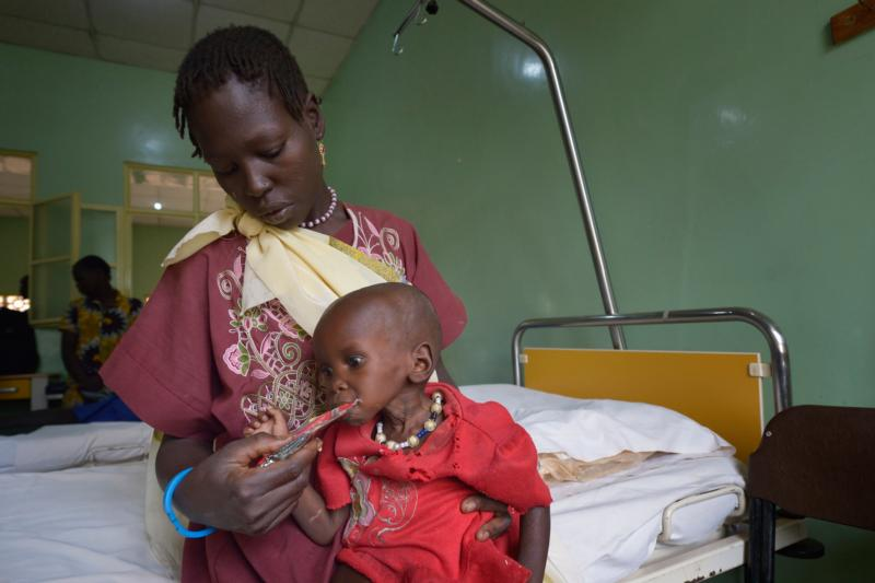 Ajok Uogu feeds her 2-year old daughter, Awok, a nutritional supplement April 26 in St. Daniel Comboni Catholic Hospital in Wau, South Sudan. (CNS photo/Paul Jeffrey)