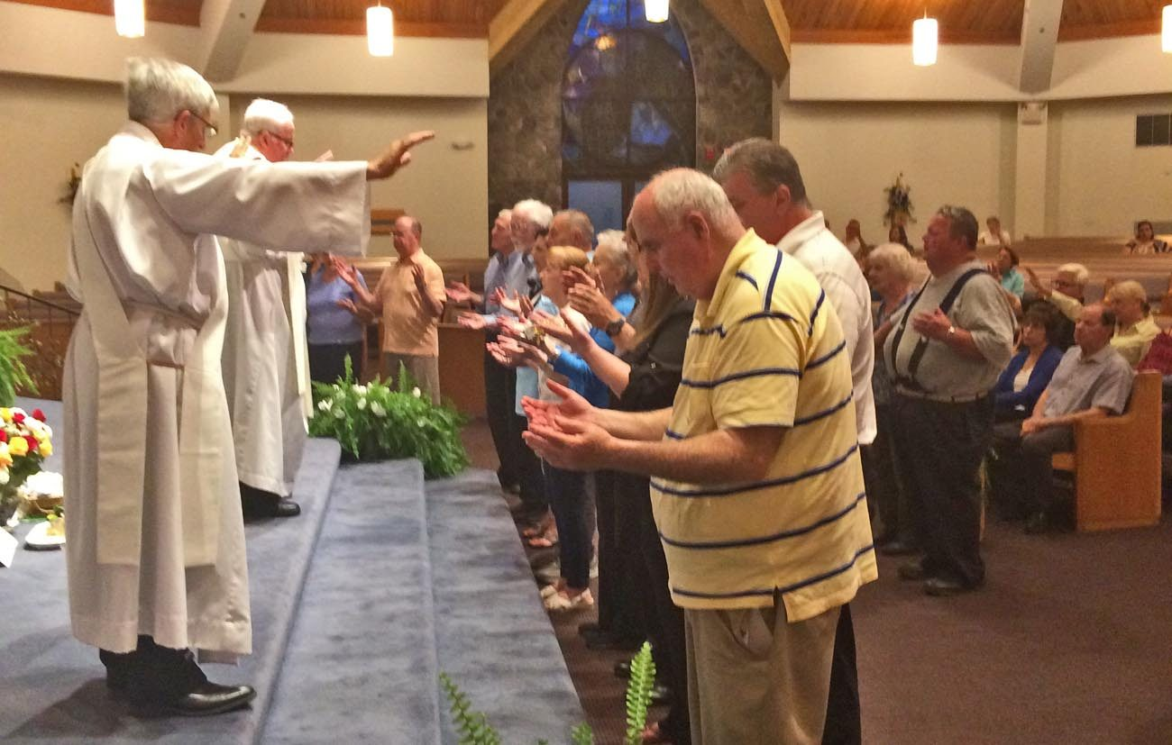 Father Francis Groarke and a deacon pray over people attending a Charismatic healing Mass May 19 at St. Thomas the Apostle Parish, Glen Mills.