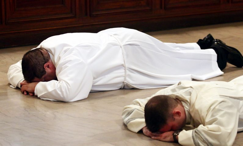 Brandon Artman and Kyle Adamczyk lay prostate on the chapel floor during their ordination Mass.