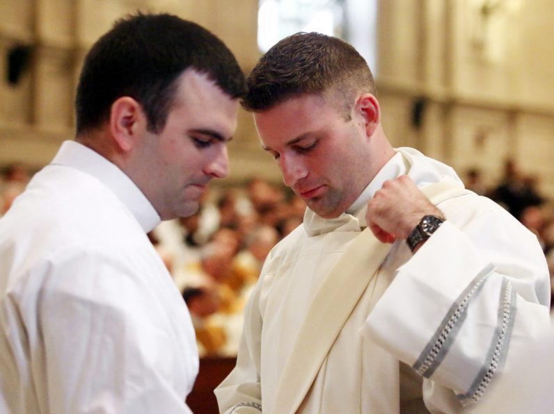 New Transitional Deacon Kyle Adamczyk (right) wears the stole of a deacon for the first time.