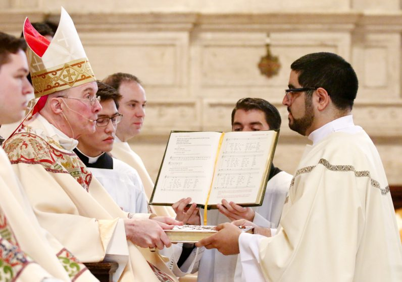 Manual Flores receives the Book of Gospels during his ordination as a transitional deacon.