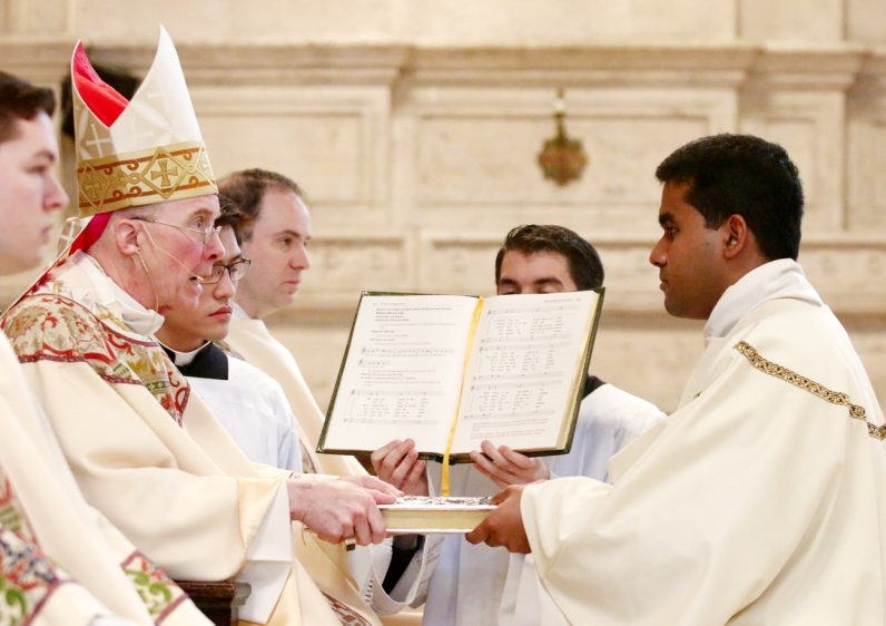 Bishop Timothy Senior hands the Book of Gospels to Shalindra Kotikawatte during his ordination as a transitional deacon.