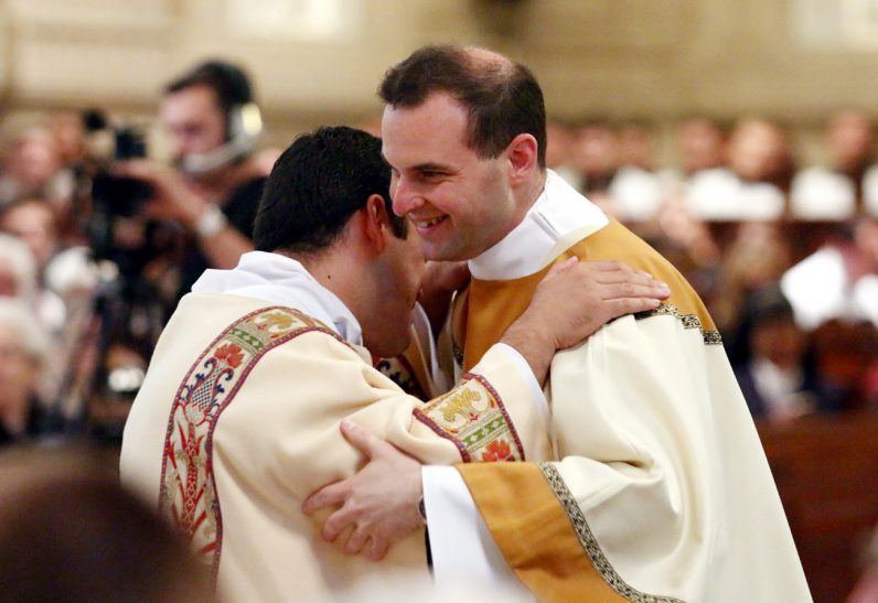 Eric Banecker exchanges a fraternal kiss with a fellow deacon.