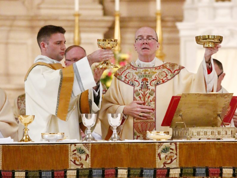Deacon Kyle Adamczyk (left) elevates the chalice while serving as deacon of the Eucharist.
