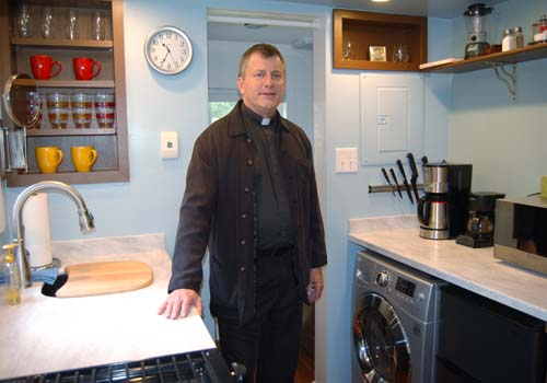 Father Peter Y. Williams, pastor of Maternity of the Blessed Virgin Mary Parish in Springfield, Vt., shows the kitchen area of his tiny house. (CNS photo/Cori Fugere Urban, Vermont Catholic)