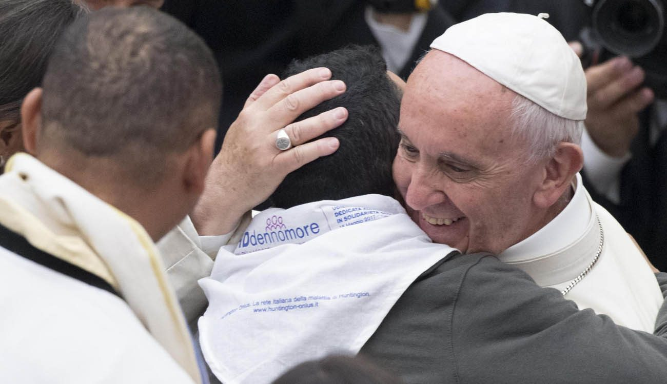 Pope Francis embraces a patient with Huntington's disease during the pontiff's general audience in St. Peter's Square at the Vatican May 17. (CNS photo/Claudio Peri, EPA)