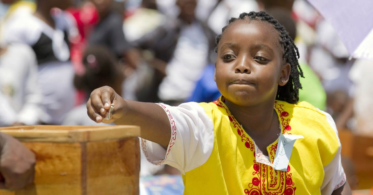 A girl makes an offering during Mass in 2011 marking Missionary Childhood Day in Nairobi, Kenya. Making connections -- including on the child-to-child level -- drives the work of the Pontifical Mission Societies. (CNS photo/Nancy Wiechec)