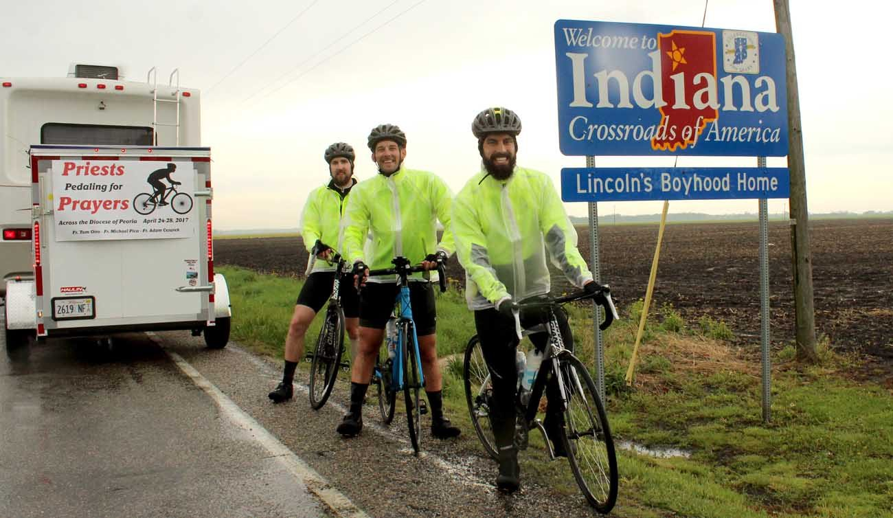 "After riding a little more than 340 miles over five days, Father Michael Pica, Father Adam Cesarek and Father Tom Otto stand just inside Indiana April 28, bringing ""Priests Pedaling for Prayers"" to a close. Behind them is one of the support vehicles that accompanied them on the journey to raise prayers for and awareness of vocations. (CNS photo/Jennifer Willems, The Catholic Post)"