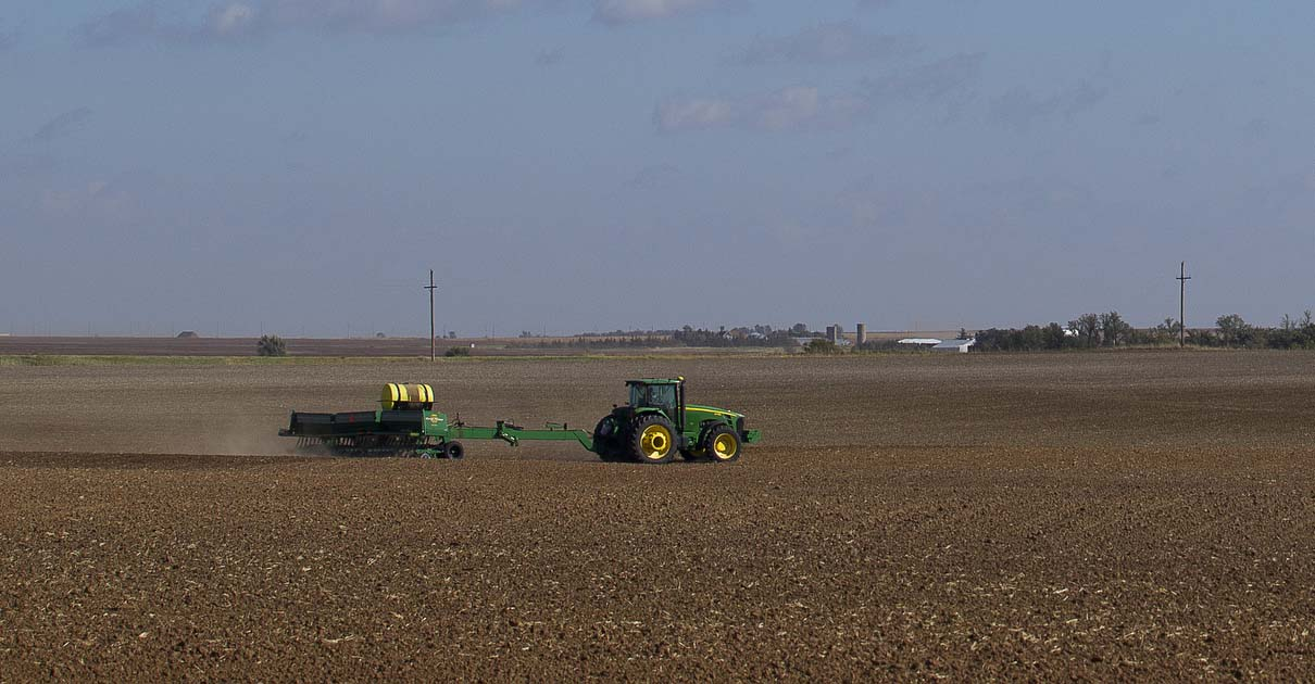 "A tractor plows a field in 2013 on a farm in St. Leo, Kan. Many family farmers in the United States are facing the worst combination of events since the ""farm crisis"" of the mid-1980s. (CNS photo/Tyler Orsburn)"