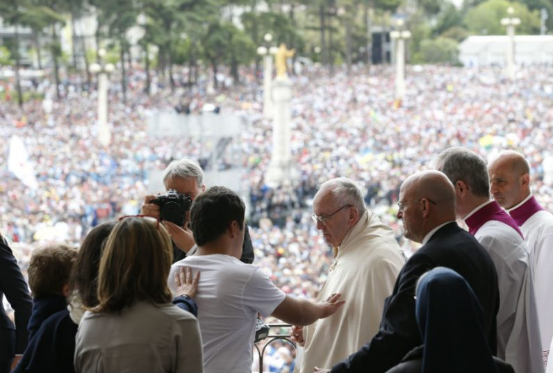 A man reaches to touch Pope Francis after the pope blessed the sick with the Eucharist at the conclusion of the canonization Mass of Sts. Francisco and Jacinta Marto, two of the three Fatima seers, at the Shrine of Our Lady of Fatima in Portugal May 13. The Mass marked the 100th anniversary of the Fatima Marian apparitions, which began on May 13, 1917. (CNS photo/Paul Haring)