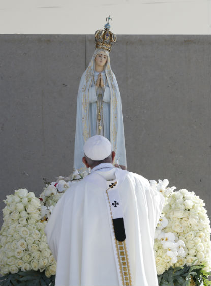 Pope Francis uses incense as he venerates a statue of Our Lady of Fatima during the canonization Mass of Sts. Francisco and Jacinta Marto, two of the three Fatima seers, at the Shrine of Our Lady of Fatima in Portugal, May 13. (CNS photo/Paul Haring)