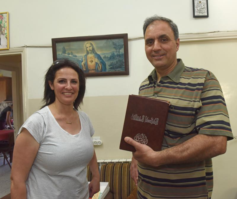 Suad and Charlie Kattan pose while holding a Bible in their home June 5 in Beit Jala, West Bank. The couple won the Adult Bible Contest of the Holy Land May 20. (CNS photo/Debbie Hill)