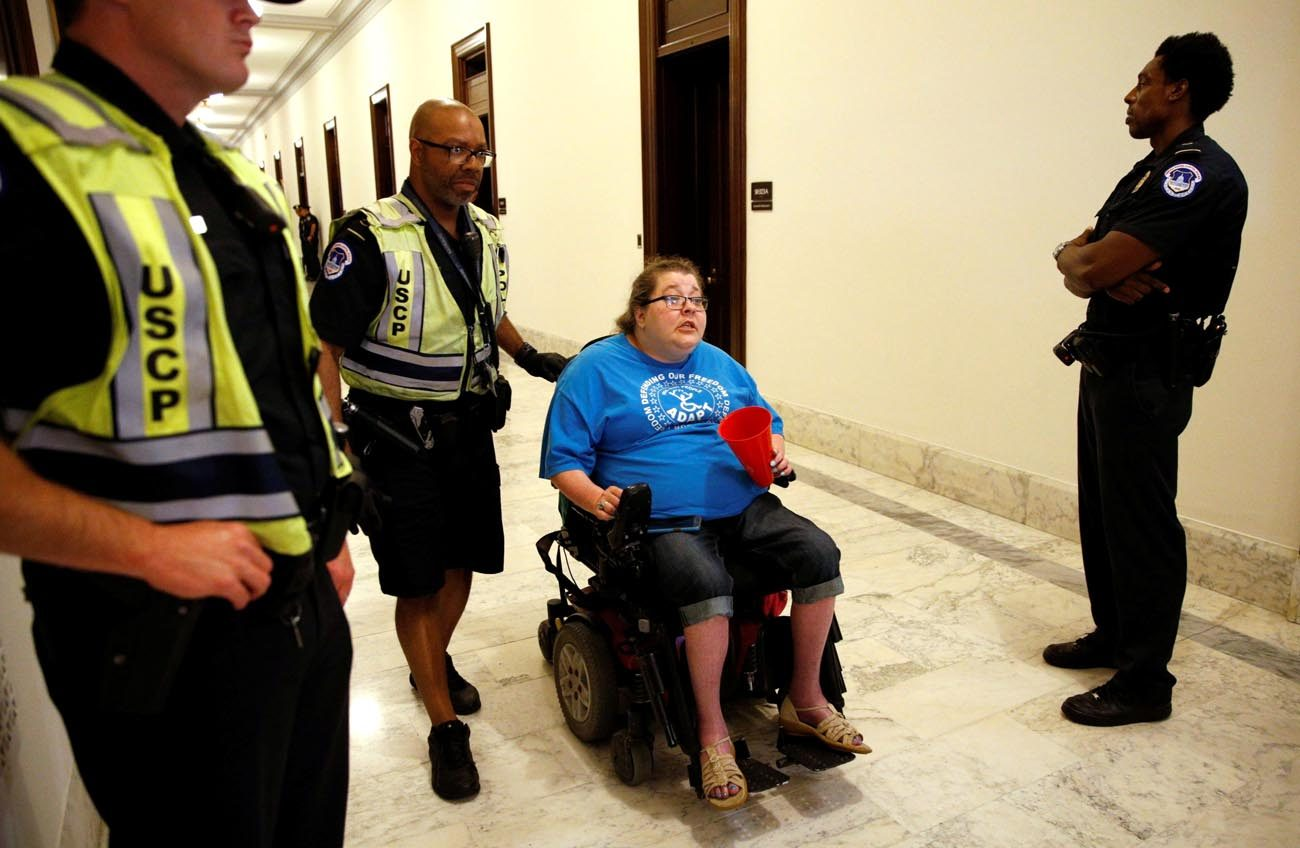 A protester demonstrating against the Senate health care bill is escorted away by police outside Senate Majority Leader Mitch McConnell's constituent office in Washington June 22. (CNS photo/Kevin Lamarque, Reuters)