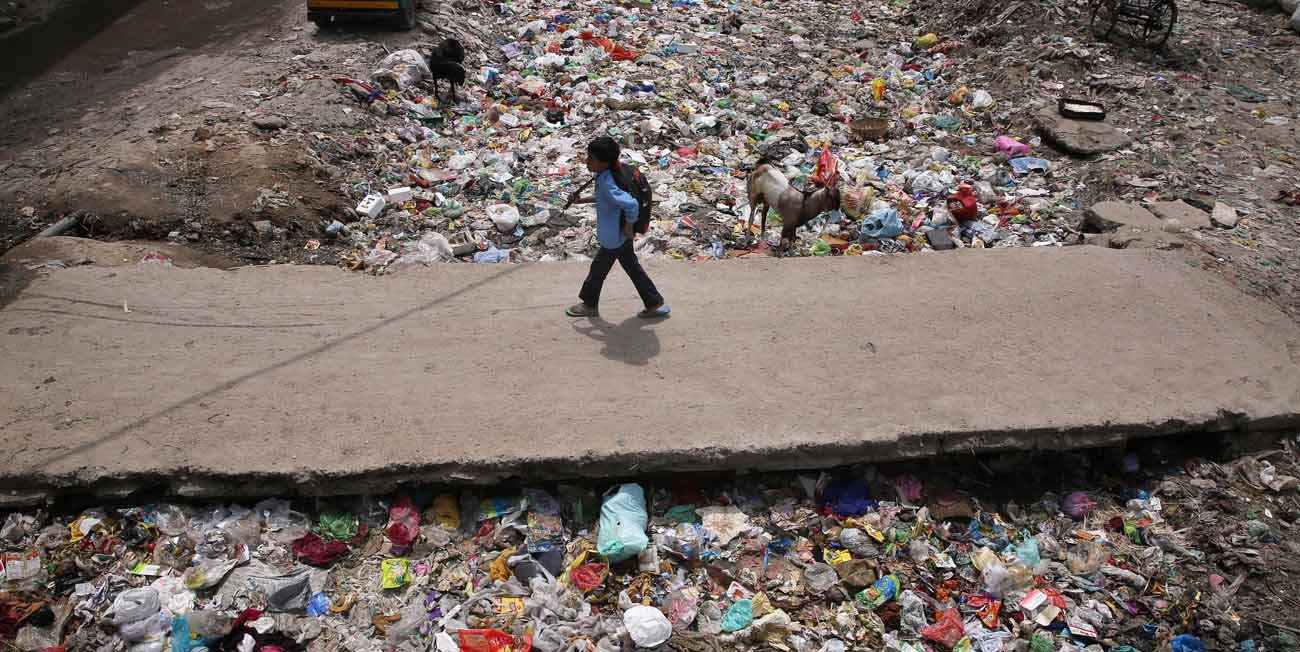 A child walks across a drain filled with garbage in New Delhi in this April 22, 2017, file photo. A priest in the north Indian state of Rajasthan is fighting to end discrimination against children whose parents live with HIV, the virus that causes AIDS. (CNS photo/Rajat Gupta, EPA)