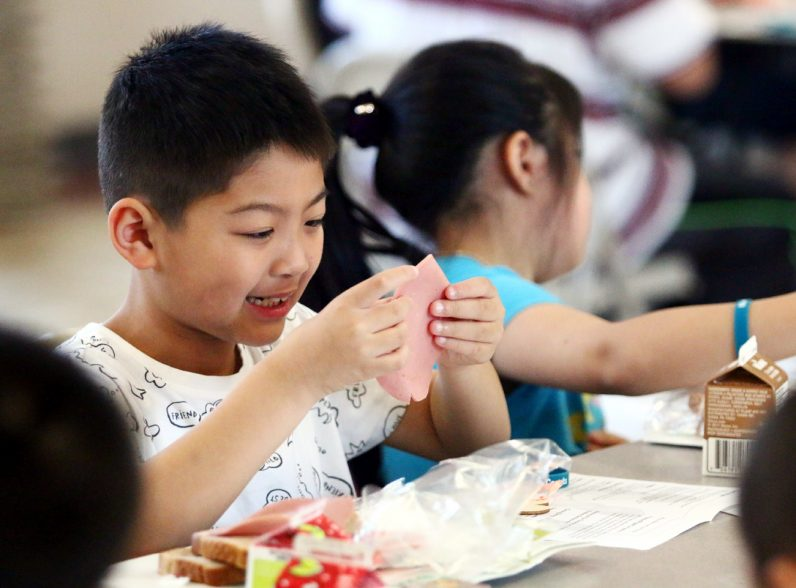 Lanson Chen is excited to see what was in the lunch box provided by NDS Summer Meals Program.