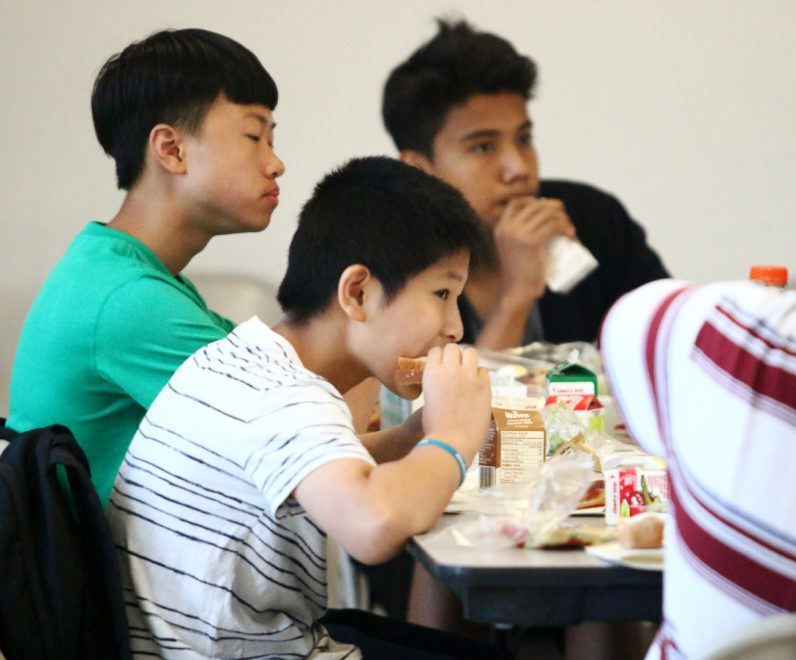 Jason Qiu takes a bite of his sandwich that he received through NDS Summer Meals Program.